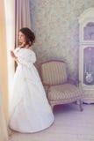 Donna in vestito d'annata di lusso che sta nella stanza luminosa Fotografie Stock