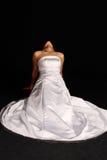 Donna in vestito da cerimonia nuziale sulle sue ginocchia Fotografie Stock