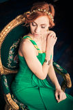 Donna in vestito da sera verde sulla sedia d'annata Fotografia Stock