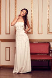 Donna in vestito da sposa bianco lungo da sera nell'interno antico L Immagini Stock