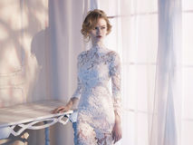 Donna in vestito dal pizzo alla finestra Fotografia Stock