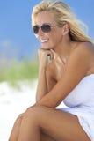 Donna in vestito ed occhiali da sole bianchi alla spiaggia Immagine Stock