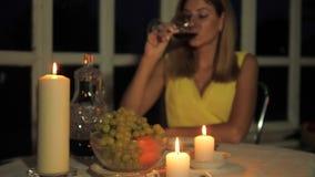 Donna in vestito giallo cenando in un ristorante a lume di candela, vino bevente stock footage