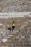 Donna in vestito giallo in occhiali da sole, anfiteatro all'aperto immagini stock
