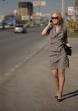 Donna in vestito grigio che cammina e che chiama dal telefono Fotografie Stock