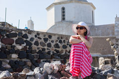 Donna in vestito lungo che si siede sulle pietre vicino alla chiesa fotografia stock