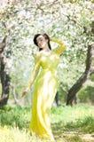 Donna in vestito lungo nel parco della mela del fiore Sorgente Immagine Stock Libera da Diritti