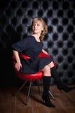 Donna in vestito nero che si siede su una sedia rossa Fotografia Stock Libera da Diritti