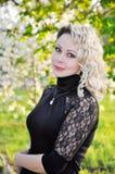 Donna in vestito nero sopra il frutteto della molla Immagine Stock