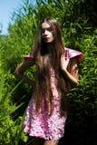 Donna in vestito rosa in alta erba verde Fotografia Stock