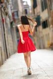 Donna in vestito rosso che cammina in via a Venezia Immagine Stock