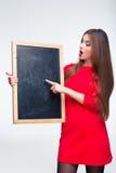 Donna in vestito rosso che indica dito sul bordo in bianco Immagini Stock Libere da Diritti