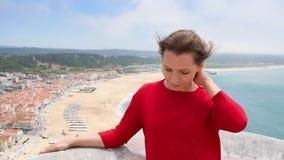 Donna in vestito rosso che si rilassa sopra una collina sopra la città di Nazaret, Portogallo archivi video