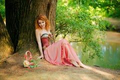 Donna in vestito rosso che si siede sotto un albero sulla natura Fotografia Stock