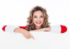 Donna in vestito rosso che tiene un tabellone per le affissioni in bianco Immagine Stock