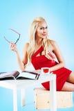 Donna in vestito rosso che tiene una rivista Fotografie Stock