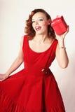 Donna in vestito rosso con il contenitore di regalo Fotografia Stock