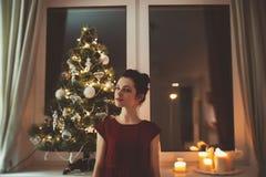 Donna in vestito rosso sopra il fondo dell'albero di Natale Fotografia Stock