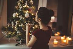 Donna in vestito rosso sopra il fondo dell'albero di Natale Immagini Stock