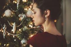 Donna in vestito rosso sopra il fondo dell'albero di Natale Fotografie Stock