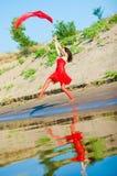 Donna in vestito rosso sul litorale Fotografie Stock