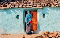 Donna in vestito variopinto dai sari che viene nella vecchia casa, India Camera della famiglia asiatica ordinaria nella zona rura fotografia stock libera da diritti
