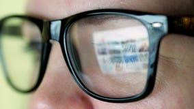 Donna in vetri che considera il monitor e che pratica il surfing Internet video d archivio