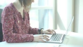 Donna in vetri con il kare dei capelli di scarsità ed anelli sulle sue dita, esaminando lo schermo del computer portatile ed i pu video d archivio