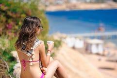 Donna in vetri con la tazza che si siede sulla spiaggia e sugli sguardi in mare fotografia stock
