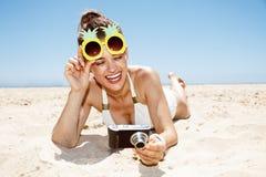 Donna in vetri dell'ananas che controlla foto alla spiaggia sabbiosa Fotografie Stock Libere da Diritti