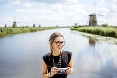 Donna vicino ai vecchi mulini a vento nei Paesi Bassi Fotografie Stock Libere da Diritti