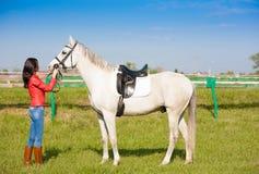 Donna vicino al cavallo giorno altezza completa Bomber rosso fotografia stock