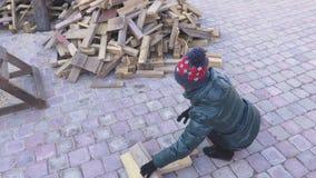 Donna vicino al mucchio della legna da ardere
