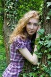 Donna vicino all'albero con la pianta dello scalatore Immagine Stock