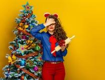 Donna vicino all'albero di Natale che tiene presente indesiderato Immagini Stock