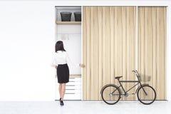 Donna vicino all'costruita nel wadrobe in una stanza con la bici Immagini Stock