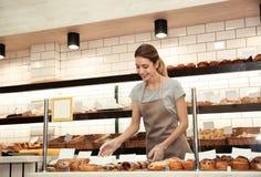 Donna vicino alla vetrina con le pasticcerie nel negozio del forno fotografie stock libere da diritti