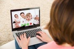 Donna Videochatting con la famiglia sul computer portatile Fotografie Stock