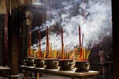 Donna vietnamita in vestito tradizionale ao DAI che prega con il bastone di incenso nel vaso bruciante della pagoda cinese in Ho  Fotografia Stock