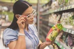 Donna vigile che legge sul prodotto in negozio Fotografia Stock