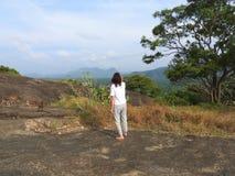 Donna, vista posteriore che esamina scimmia selvaggia in natura, Dambulla, Sri Lanka immagini stock