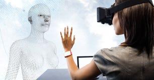 Donna in VR allo scrittorio davanti al codice binario a forma di femminile 3D contro il cielo e le nuvole Fotografia Stock