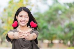 Donnant l'amour dans le jour du ` s de valentine, la prise asiatique de main de femme donnent bel aimer rouge de bonbon à coeur Photographie stock