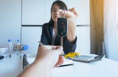 Donnant la clé de voiture en main pour l'accord de ventes de véhicule, les finances de voiture et le concept de prêt image libre de droits