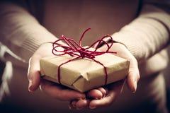 Donnant un cadeau, présent fait main enveloppé en papier photos libres de droits