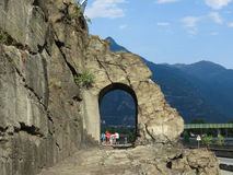 Ancient roman road arch in Donnas. DONNAS, ITALY - CIRCA AUGUST 2017: Ancient roman consular road stone arch with tourists taking a group photo Royalty Free Stock Image
