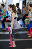 Donne adatte che eseguono allungando esercizio con la banda di resistenza Immagine Stock