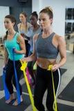 Donne adatte che eseguono allungando esercizio con la banda di resistenza Immagini Stock Libere da Diritti