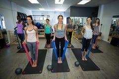 Donne adatte che eseguono allungando esercizio con la banda di resistenza nella palestra Immagini Stock
