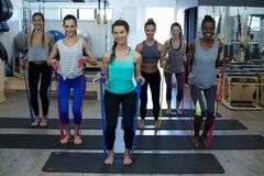 Donne adatte che eseguono allungando esercizio con la banda di resistenza nella palestra Fotografie Stock Libere da Diritti